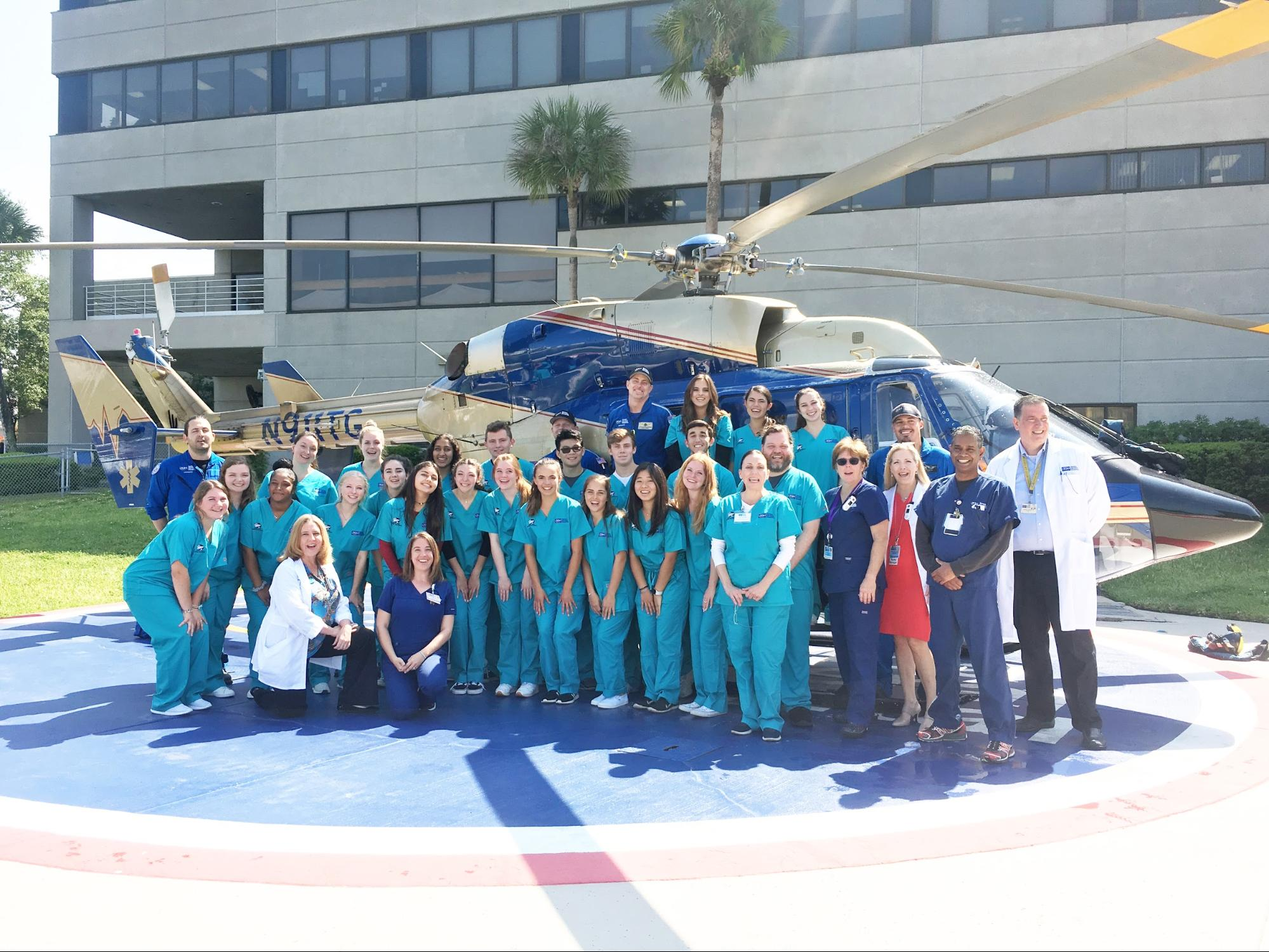 Students in the Medical Explorers Club pose in front of a medical helicopter at Tampa General Hospital