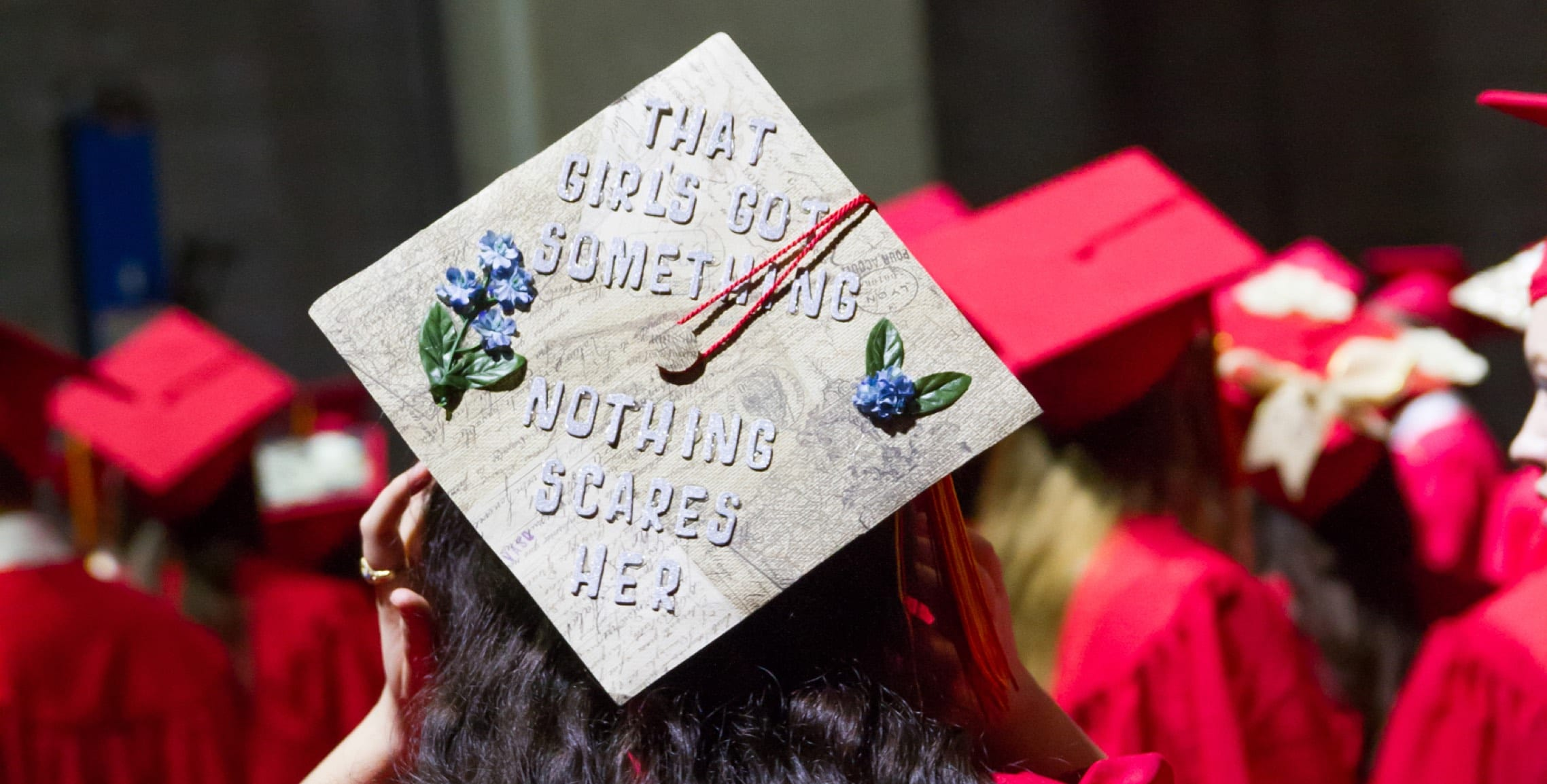 Girl wearing graduation hat that says Nothing Scares Her