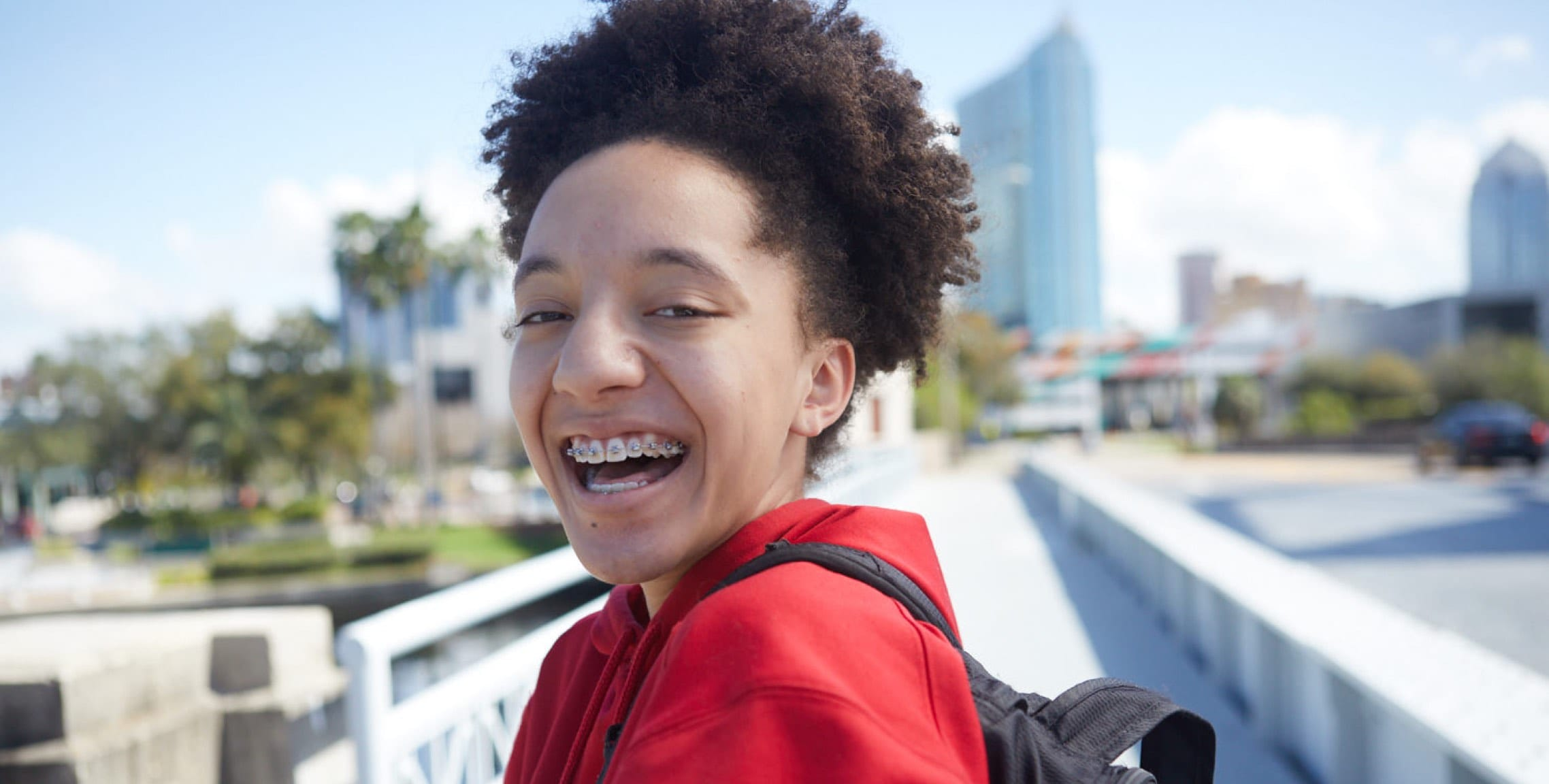 Student smiling with backpack and walking over bridge into downtown Tampa