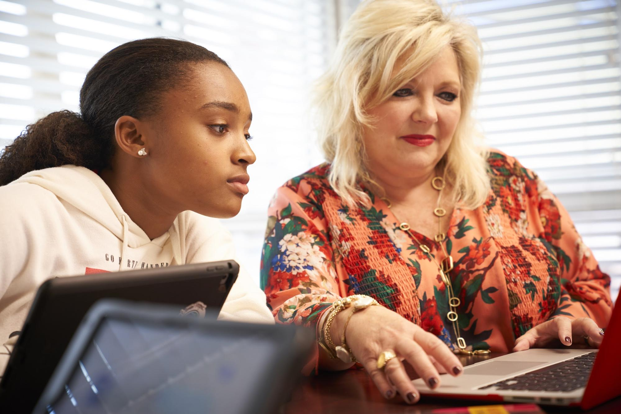 Student looking over teacher's shoulder at laptop