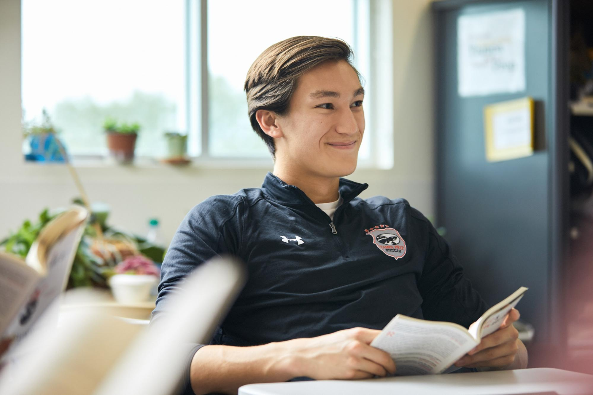 Boy smiling with book in English class