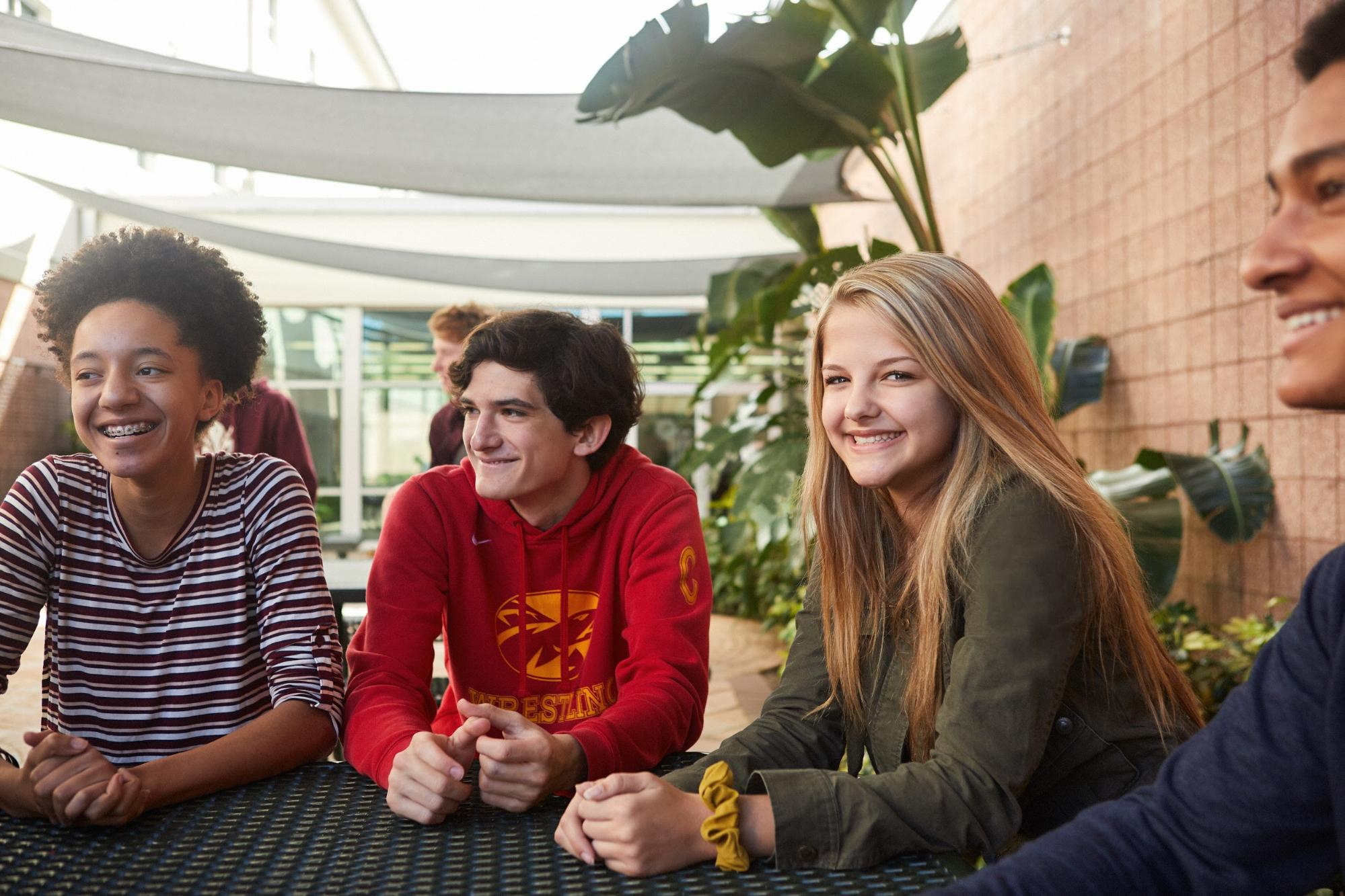 students having a discussion at outdoor picnic table in Tampa Prep atrium