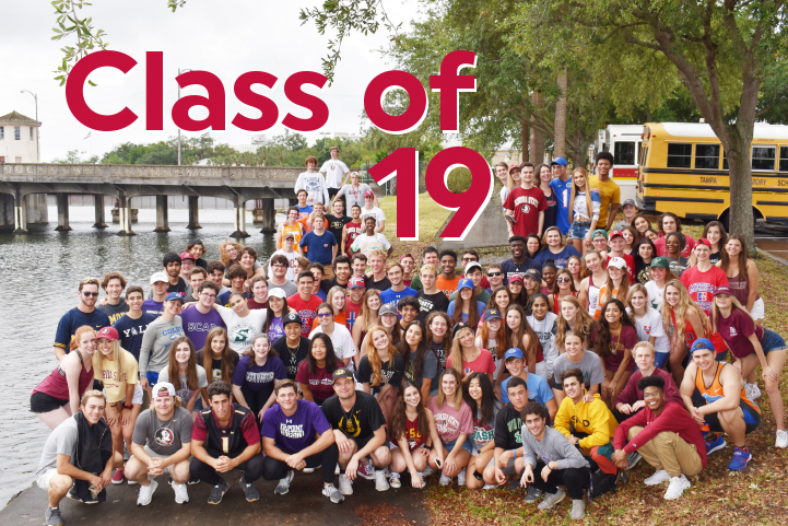The Class of 2019 wearing college t-shirts sitting by the river