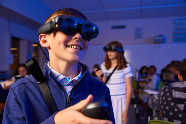 middle school boy using virtual reality googles in science class