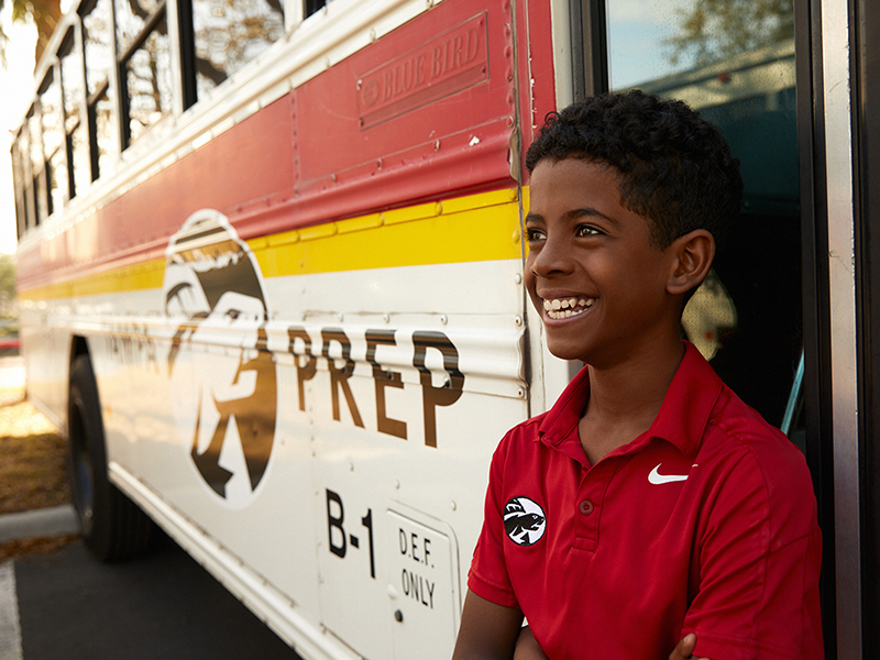 middle school boy leaning against a Tampa Prep bus