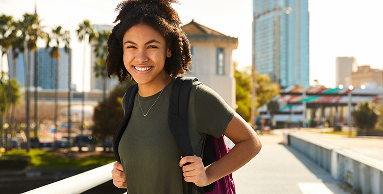 girl with backpack stands on downtown bridge