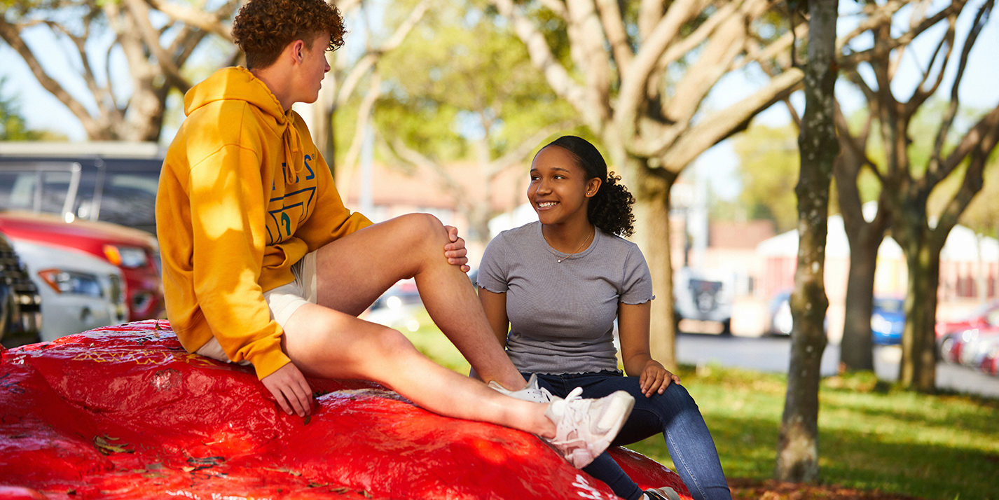 students sit on red rock in tampa prep parking lot