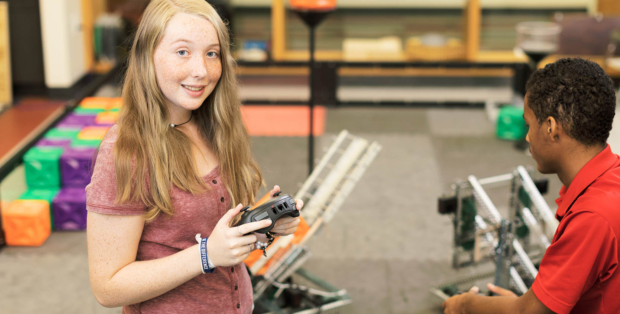girl stands with robotics remote control in a makerspace